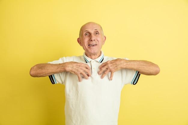 Portrait de l'homme senior caucasien isolé sur mur jaune