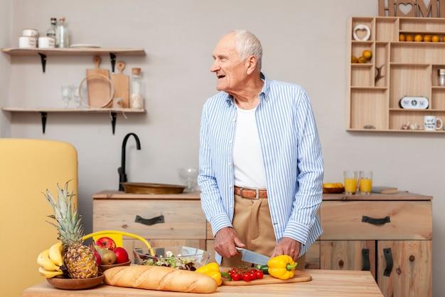 Portrait d'homme senior, couper les légumes