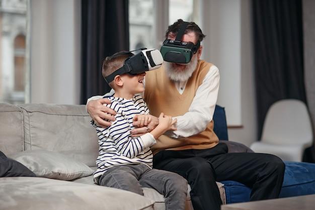 Portrait d'un homme senior excité à l'aide de lunettes vr assis sur un canapé à la maison avec un petit-fils qui rit à côté de lui