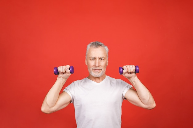 Portrait d'un homme senior exerçant avec des haltères.