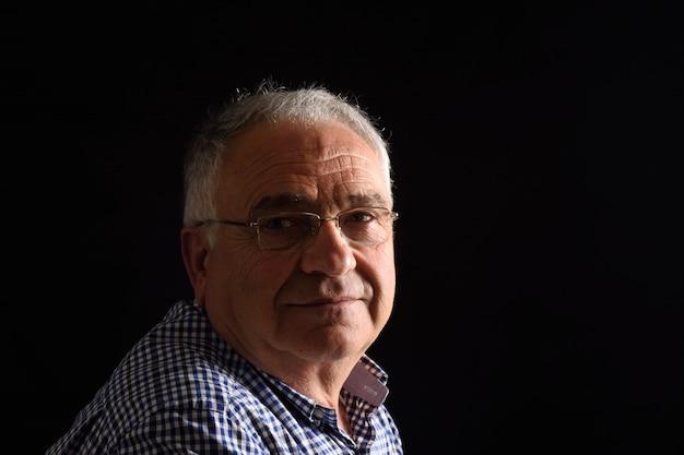 Portrait d'un homme senior avec un fond noir