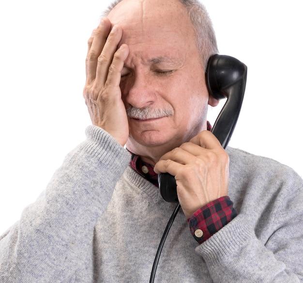 Portrait d'un homme senior frustré parlant sur un ancien téléphone fixe sur fond blanc