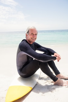 Portrait d'un homme senior heureux en combinaison de plongée assis sur une planche de surf