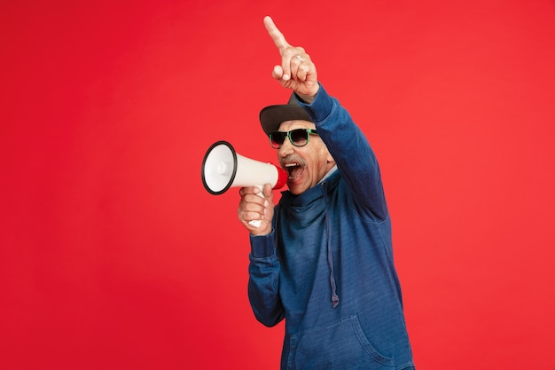 Portrait d'homme senior hipster à l'aide d'appareils, gadgets isolés sur fond de studio lumineux.