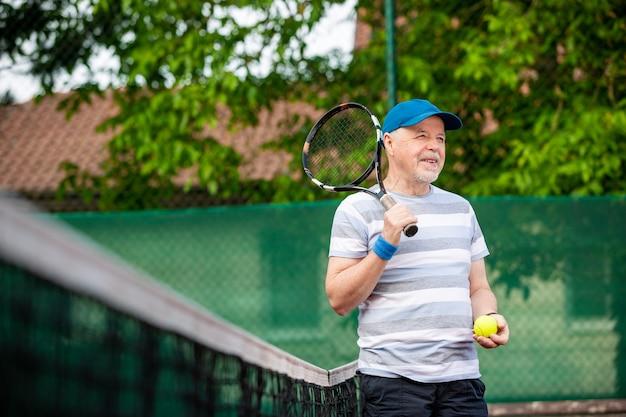 Portrait d'un homme senior jouant au tennis dans un sport à l'extérieur, à la retraite, concept sportif
