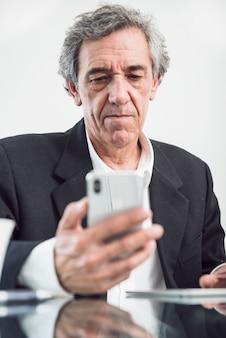 Portrait d'homme senior en regardant smartphone