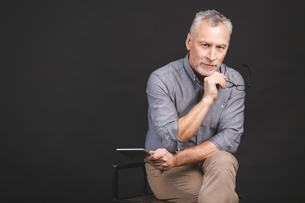 Portrait d'un homme senior à la retraite tenant dans sa main une tablette numérique en position assise, tenant des lunettes.