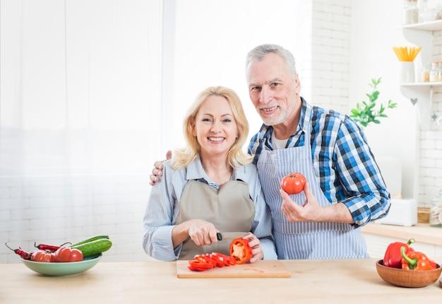 Portrait d'un homme senior avec sa femme, couper les poivrons