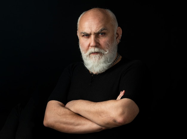 Portrait d'un homme senior sérieux sur fond noir.