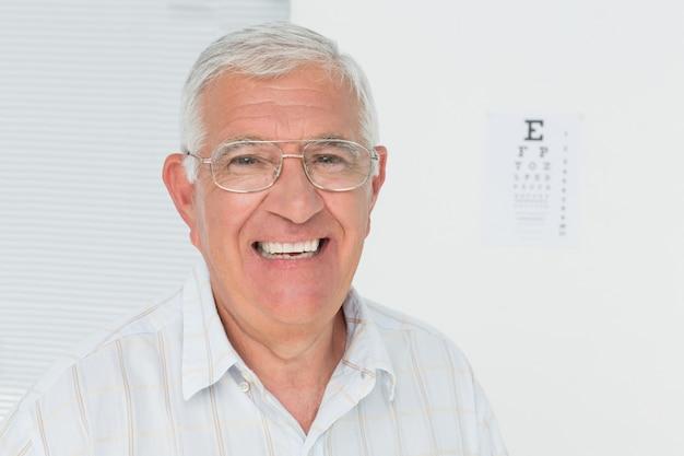 Portrait d'un homme senior souriant avec le tableau de l'oeil en arrière-plan