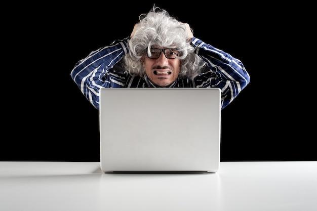 Portrait d'un homme senior stressé travaillant sur un ordinateur portable assis à une table blanche sur fond noir