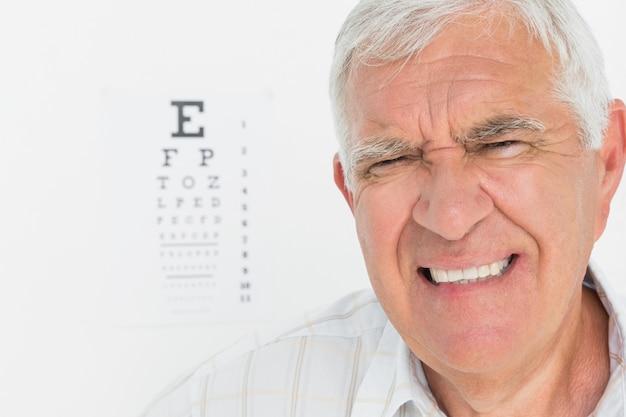 Portrait d'un homme senior avec le tableau de l'oeil en arrière-plan