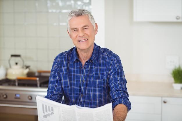 Portrait d'homme senor lisant le journal dans la cuisine