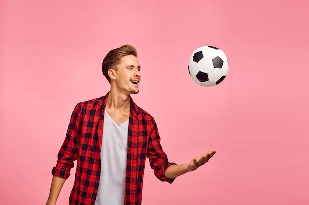 Portrait d'homme sérieux avec ballon de football, fond rose, émotion