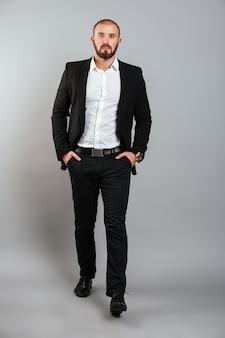 Portrait d'un homme sérieux en costume professionnel posant devant la caméra avec les mains dans les poches, isolé sur mur gris