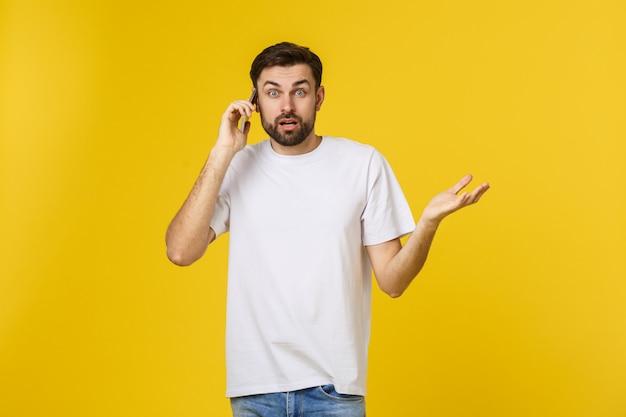 Portrait d'un homme sérieux parlant au téléphone isolé.