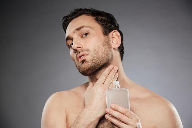 Portrait d'homme sexuel masculin mettant le parfum après-rasage sur son cou, isolé sur mur gris