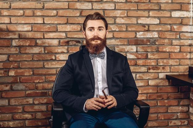 Portrait d'un homme sexy et élégant avec une moustache et une barbe assis sur une chaise et tenant un verre de whisky et un cigare à la main, posant contre un mur de briques. concept de l'ego masculin