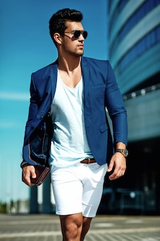 Portrait d'homme sexy mannequin homme beau habillé en costume élégant posant dans la rue. ciel bleu