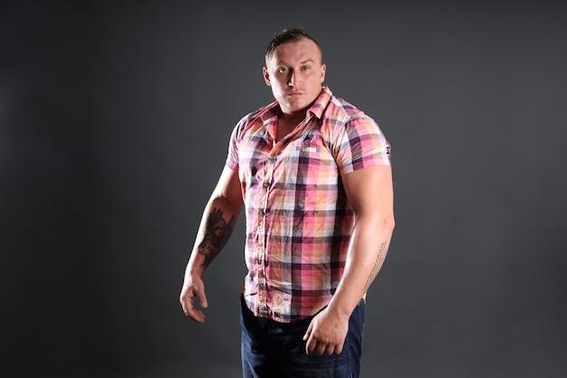 Portrait d'un homme sexy sportif avec tatouage. parfaite silhouette, biceps et larges épaules