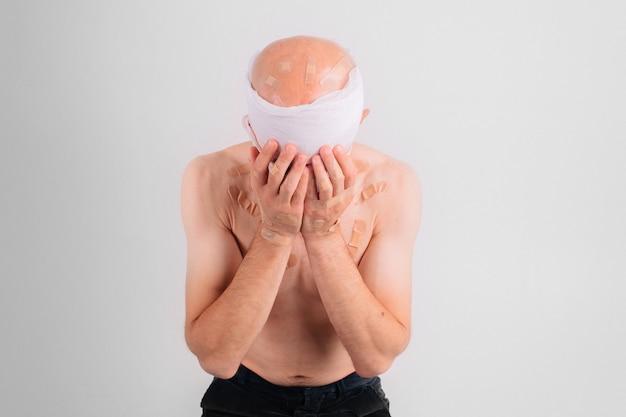 Portrait d'un homme souffrant avec une tête bandée se sentant mal et couvre le visage avec ses mains