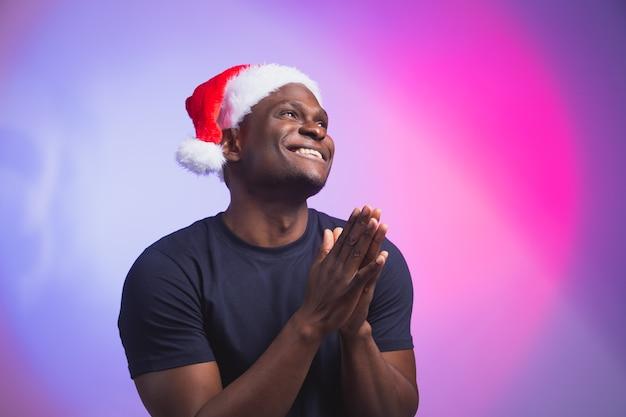 Portrait d'un homme souriant afro-américain positif en bonnet de noel et t-shirt décontracté sur coloré