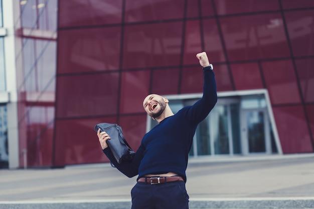 Portrait d'un homme souriant aux poings levés