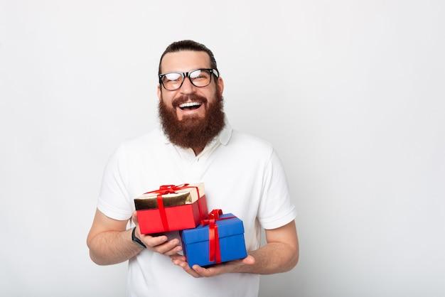 Portrait d'homme souriant avec barbe tenant deux coffrets cadeaux sur fond blanc
