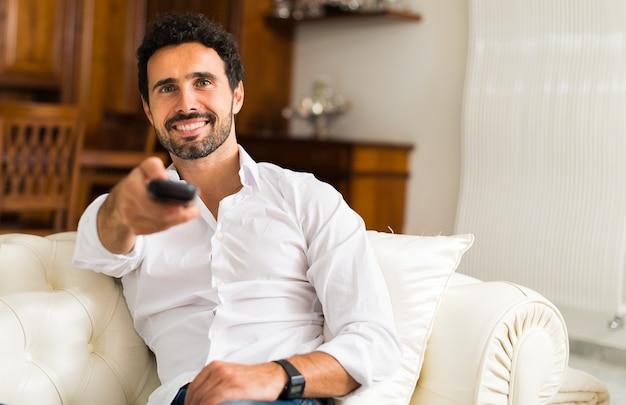 Portrait d'un homme souriant choisissant un programme à regarder à la télévision