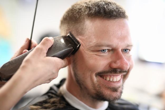 Portrait d'homme souriant dont le maître coupe à la machine.