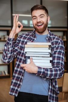 Portrait, de, a, homme souriant, étudiant, tenue, livres, dans, bibliothèque