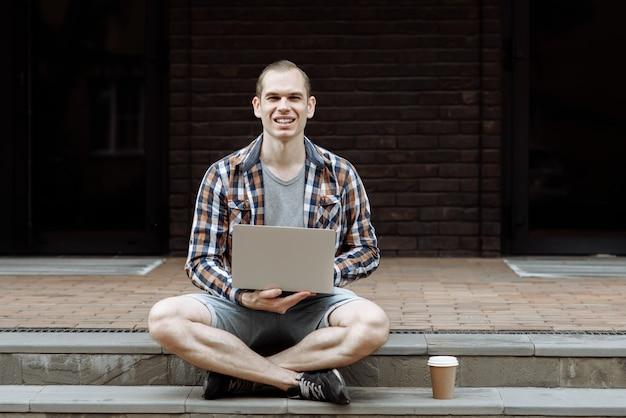 Portrait d'un homme souriant positif avec ordinateur portable et café assis sur le paysage urbain
