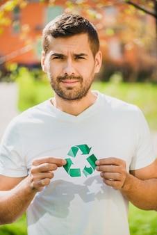 Portrait d'un homme souriant, tenant l'icône du recyclage dans le parc