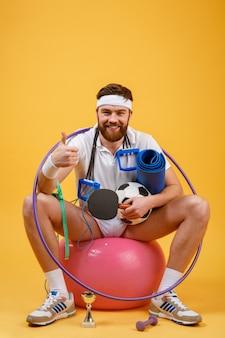 Portrait d'un homme de sport assis sur un ballon de fitness