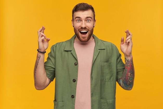 Portrait d'homme surpris aux cheveux bruns et à la barbe. vêtu d'une veste verte à manches courtes. a des tatouages. croise les doigts, fait un vœu. isolé sur mur jaune