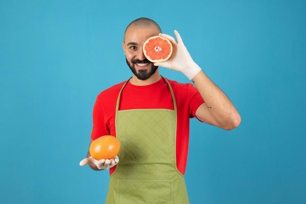 Portrait d'un homme en tablier et gants tenant des pamplemousses frais.