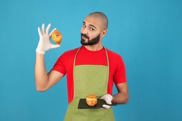 Portrait d'un homme en tablier et gants tenant des pâtisseries fraîches.