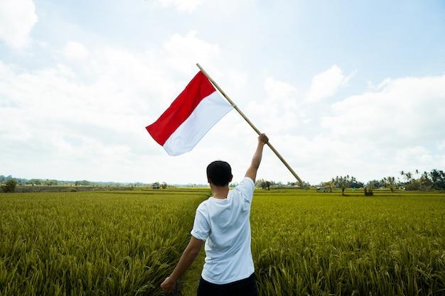 Portrait d'homme tenant un drapeau de l'indonésie