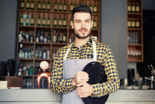 Portrait d'homme tenant un plateau dans le bar