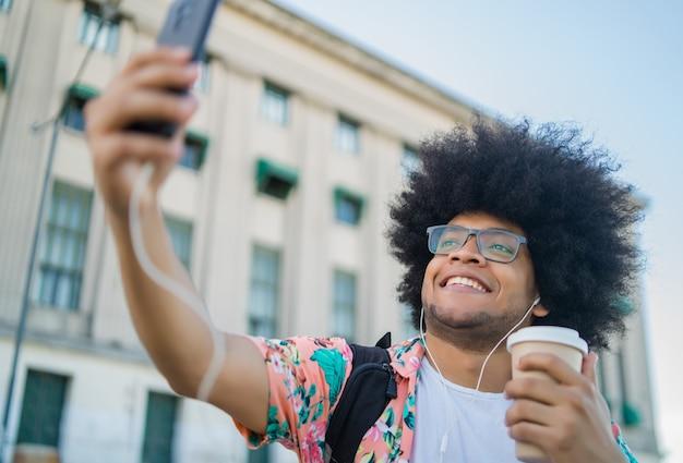 Portrait d'un homme tenant une tasse de café et prenant un selfie avec un téléphone mobile en se tenant debout à l'extérieur dans la rue