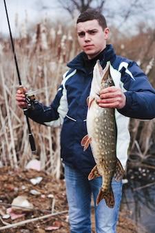 Portrait, homme, tenue, grand, attrapé, poisson, et, canne à pêche