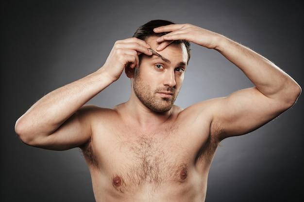 Portrait d'un homme torse nu confiant plumant des sourcils
