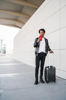 Portrait d'homme de tourisme afro à l'aide de son téléphone portable et transportant une valise tout en marchant à l'extérieur dans la rue