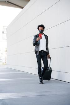 Portrait d'un homme de tourisme afro tapant au téléphone et portant une valise en marchant à l'extérieur dans la rue