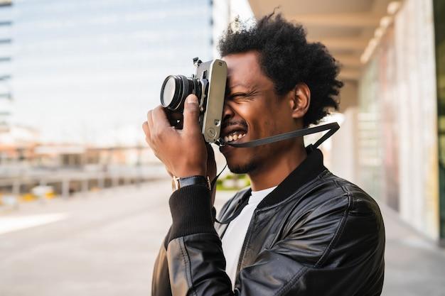 Portrait d'homme de tourisme à prendre des photos avec appareil photo tout en marchant à l'extérieur dans la rue