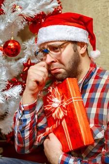 Portrait d'un homme triste avec un cadeau de noël en bonnet de noel