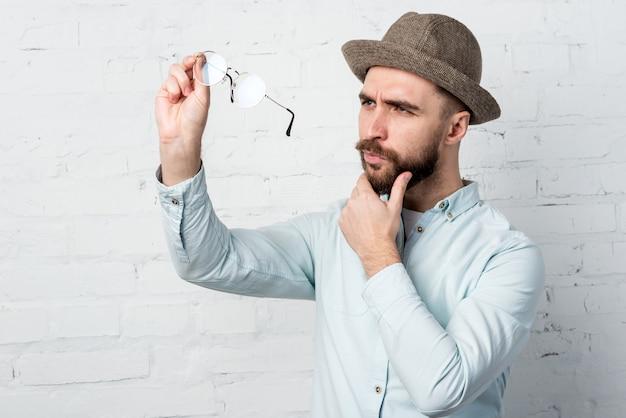 Portrait d'homme en vêtements décontractés et chapeau a enlevé des lunettes et en regardant attentivement contre un mur de briques blanches