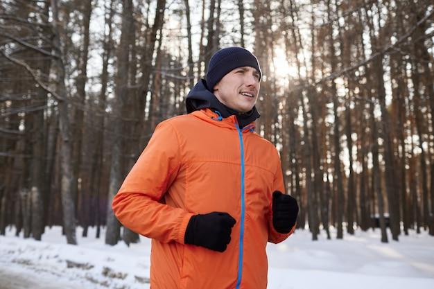 Portrait d'un homme en vêtements de sport lumineux qui traverse une forêt d'hiver. jour glacial
