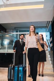 Portrait D'hommes D'affaires Arrivant à L'hôtel Et Marchant Dans Le Hall Avec Leurs Bagages. Concept De Voyage Et D'affaires. Photo Premium