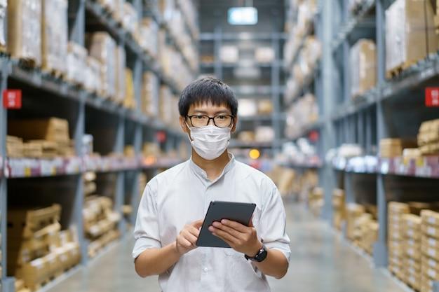 Portrait hommes asiatiques, personnel, comptage de produits responsable du contrôle d'entrepôt se tenir debout, compter et inspecter les produits dans l'entrepôt